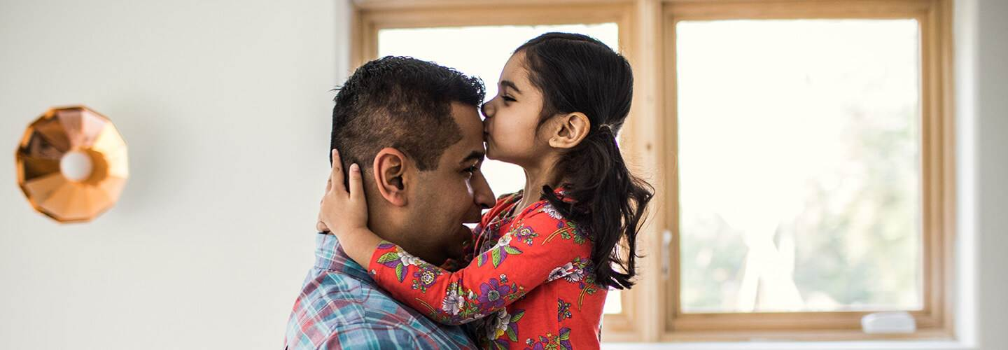 Daughter kissing her father on the forehead